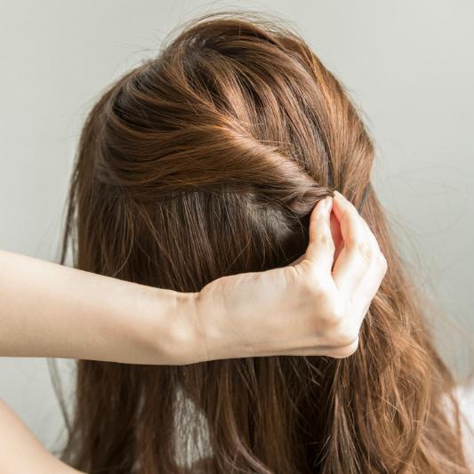 全体的に軽く巻いてから、トップの表面の髪を2つに分けたら、やや下の方に向かってねじっていく。