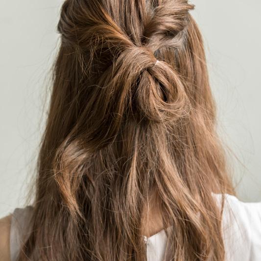 ねじった髪の束をひとつに結ぶ。毛先を最後まで引き出さずに輪っか状に残す。