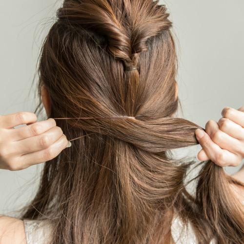 両横の髪を後ろに取り、作ったくるりんぱの下で結び、2つ目のくるりんぱを作り、毛先を引き出す。