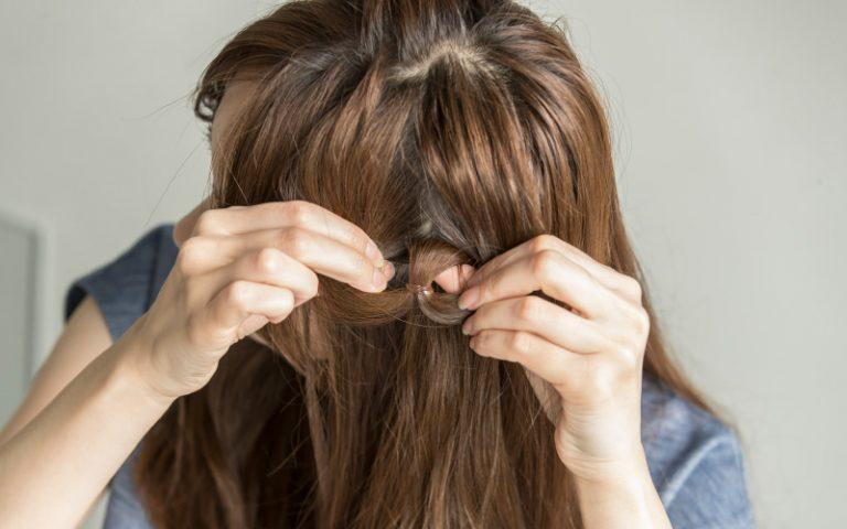 2|結んだゴムを少し下にずらし、ゴムの上に指を入れて隙間をつくり、その間に髪の束を通して《くるりんぱ》する
