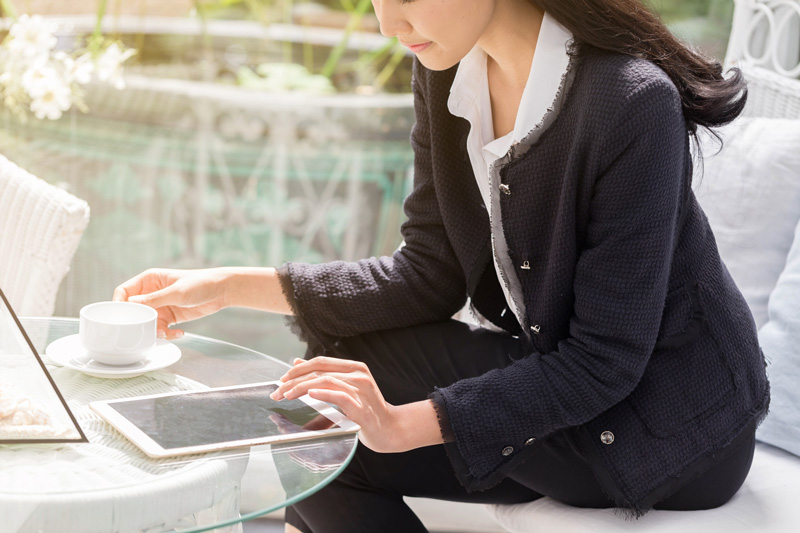 カフェでiPadをチェックする女性
