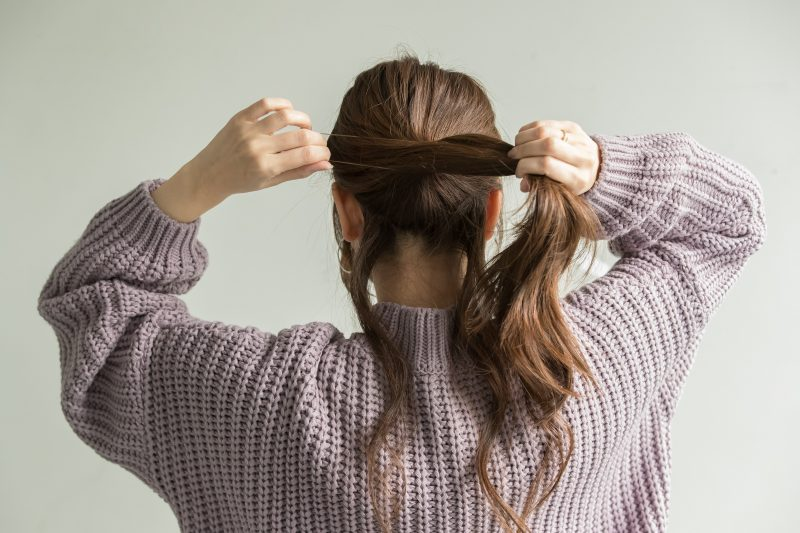 1|髪全体を軽くコテで巻いて、襟足の髪を少し残して一つに結ぶ。