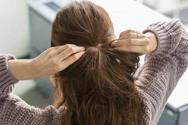 2|結んだゴムを少し下げて緩めて、内側の髪を左右に引っ張り結び目を締める。