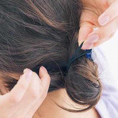 下ろした毛束を結び目に巻きつけ、最後に結び目ごとねじって締めてから、毛先をゴムに入れ込んで固定する