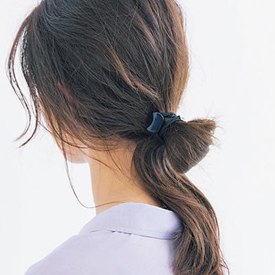 襟足の辺りで手ぐしでざっくりまとめ、ループ状に結ぶ。顔まわりの髪はキープスプレーで束感を出す