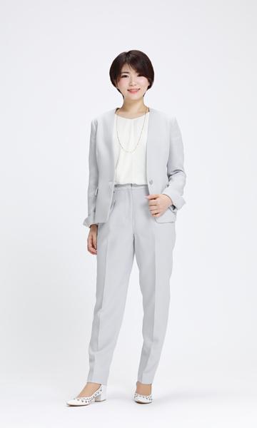 やさしげな淡いブルーグレーのパンツスーツ×白パンプス