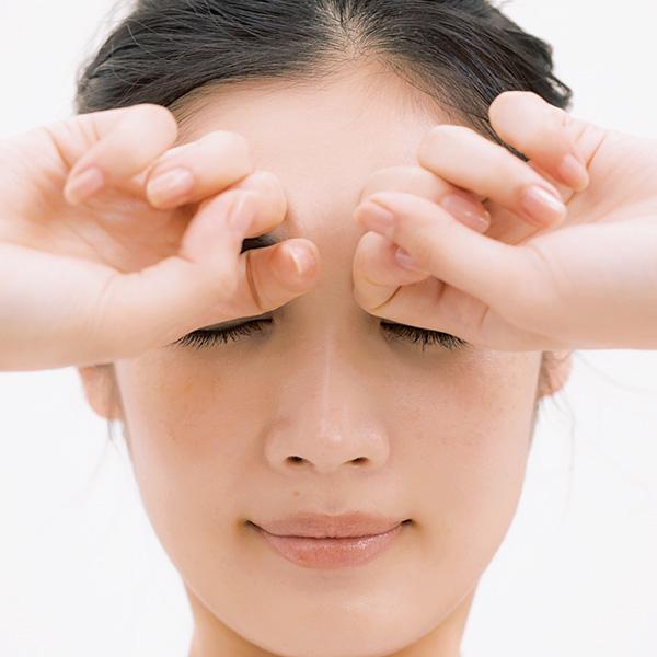 眉上の生え際を中指の第2関節で押す
