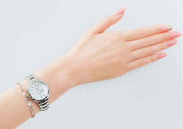 メタリックな時計のニュアンスを加えたピンクネイル