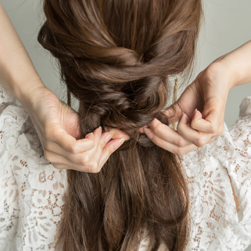 毛先までたどり着いたら、全ての髪をひとつにまとめて結ぶ。